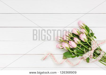 Bouquet Of Pink Roses Decorated With Lace On White Wooden Background. Top View, Copy Space