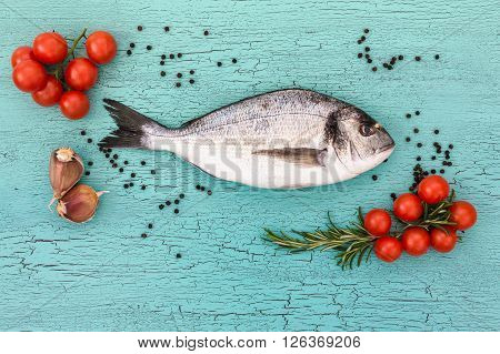 Raw Dorado Fish With Cherry Tomatoes On Blue Table. Top View, Copy Space. Raw Bream Fish