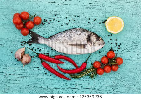 Raw Dorado Fish, Cherry Tomatoes, Garlic And Lemon On Blue Background. Top View