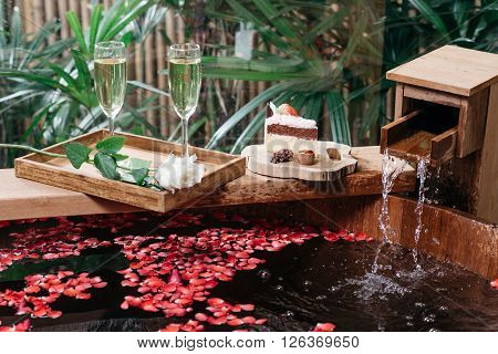 Onsen series : Wooden bathtub filled with roses petal