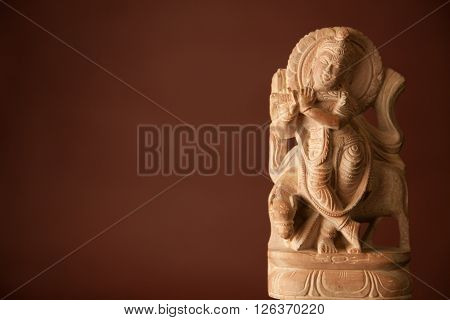 The statue of Hindu God Krishna made of marble with warm red brown background