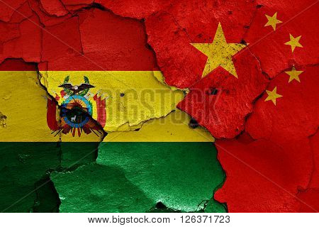 flags of Bolivia and China painted on cracked wall