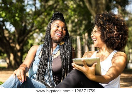 Latin women using tablet computer in the park