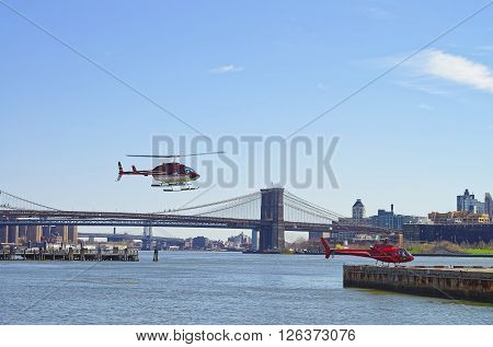 Helicopters near Brooklyn bridge and Manhattan bridge over East River. Tourists on board. Bridges connect Lower Manhattan with Brooklyn of New York USA.