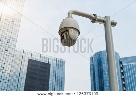 security camera with office building background against clear sky
