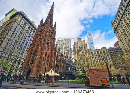 NEW YORK, USA - APRIL 24, 2015: Street view of Trinity Church in Lower Manhattan New York USA. It is a historic parish church near Wall Street and Broadway. Tourists nearby.