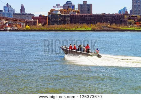NEW YORK USA - APRIL 25 2015: View on a boat and Brooklyn Heights of New York USA in East River. Tourists on board.