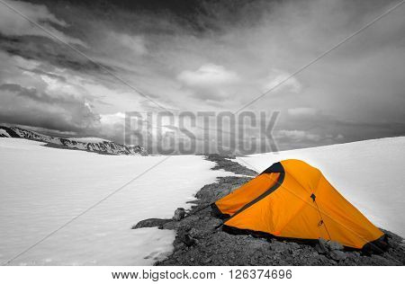 Orange tent in snow mountains. Turkey Central Taurus Mountains Aladaglar (Anti-Taurus) plateau Edigel (Yedi Goller). Selective color.