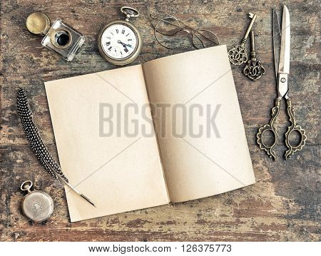 Open book and antique writing tools on wooden background. Vintage style toned picture