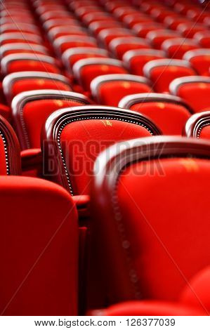 Rows of empty red velvet seats inside a theater ** Note: Shallow depth of field
