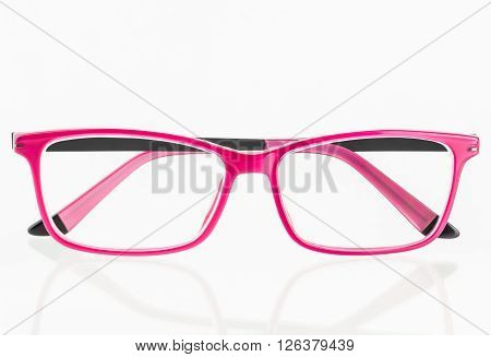 Close up of pink eye glasses with reflection on shiny white surface.