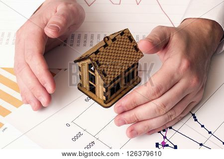 small wooden house and a male hand on the chart