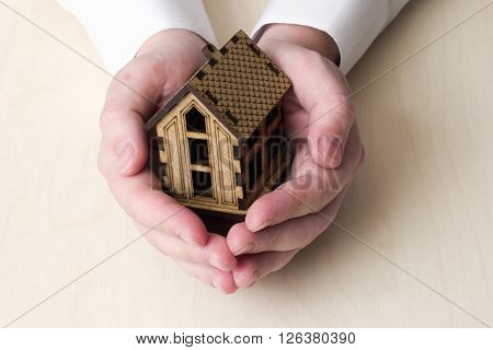 small wooden house in the hands of the man on the table