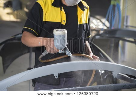 Auto body repair series : Worker painting car bumper