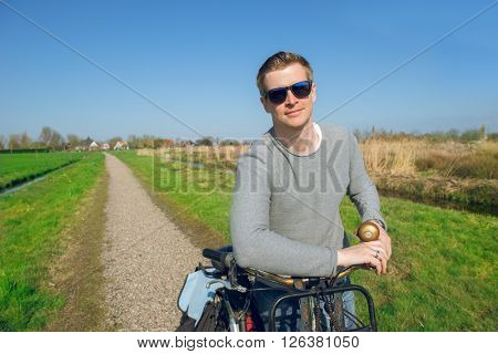 Portrait of a man standing with a bicycle  in a countryside in early spring