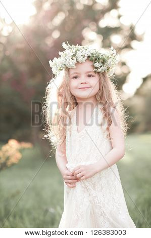 Smiling baby girl 3-4 year old wearing flower wreath outdoors. Little princess. Childhood.