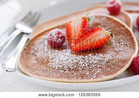 Homemade buttermilk american pancakes with fresh strawberry and raspberry on a white plate on a white table for breakfast closeup selective focus