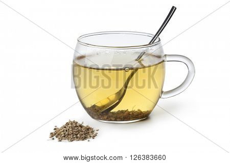 Anise tea in a glass and seeds on white background