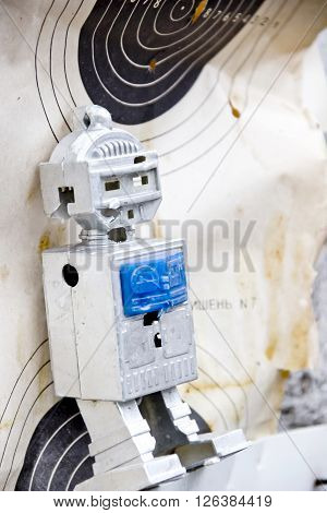 target with bullet holes and shooted toy robot