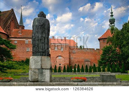Frombork Poland - July 28 2013: Nicolaus Copernicus statue in front of the Frombork Cathedral built in 1329-1388 gothic style.