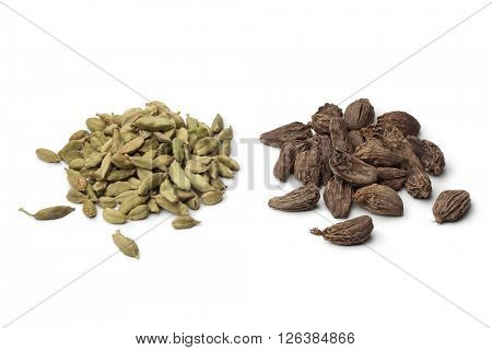 Heaps of green and large black Cardamom seeds on white background