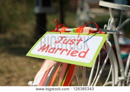White bicycle with just married sign and colorful ribbons. Outdoors.