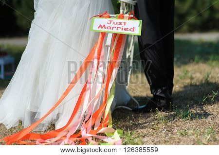 Groom and bride on white bicycle with just married sign and colorful ribbons. Outdoors. Loving couple in the background.