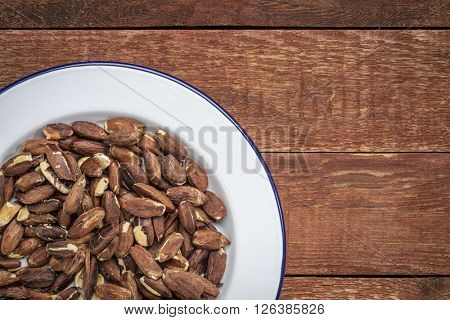 roasted pili nuts grown in Philippines, top view of nuts on white metal plate against  a rustic barn wood