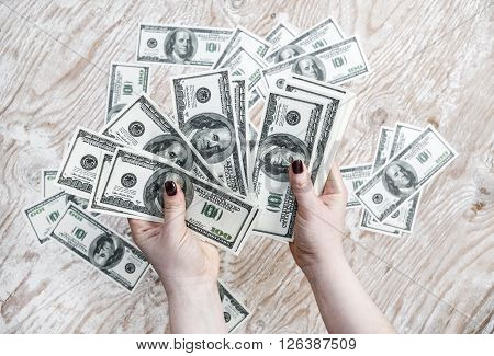 Dollars in hands. Cash in hands. Fake money in hands. Money in female hands on light wooden background.
