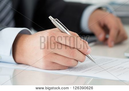 Close-up of businessman hands signing documents. Man writing something sitting at his office. Partnership agreement of contact signing closing balance or making financial report concept