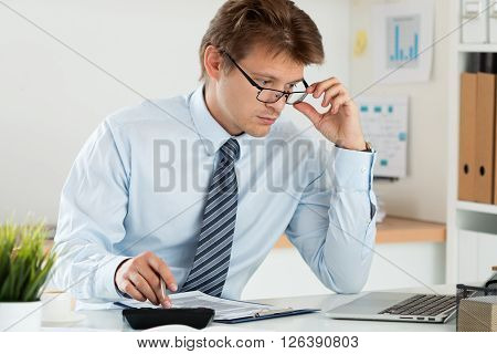 Portrait of bookkeeper or financial inspector adjusting his glasses making report calculating or checking balance. Home finances investment economy saving money or insurance concept