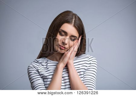 Time to sleep. Nice charming pleasant girl holding her palms together and sleeping while standing isolated on grey background