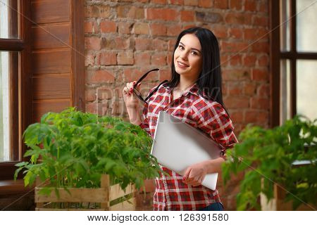 Looking closer. Portrait of a beautiful young woman posing indoors holding a laptop looking at her tomato seedlings on the table.