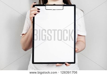 Woman holding clipboard with a blank sheet of paper. Blank paper poster in female hands. Blank template for graphic designers portfolios.
