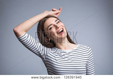 Joyful moment.  Positive content beautiful girl smiling and holding her hand on the head  while standing isolated on grey background
