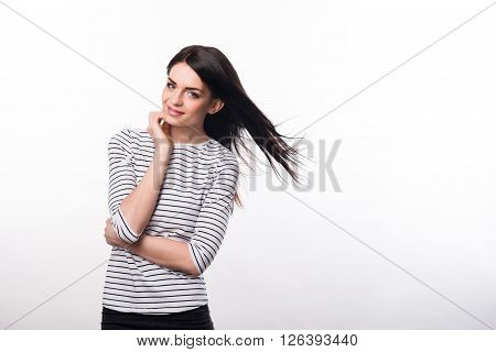 Feel the attraction. Pleasant seductive delighted girl folding her hands and smiling while standing isolated on grey background