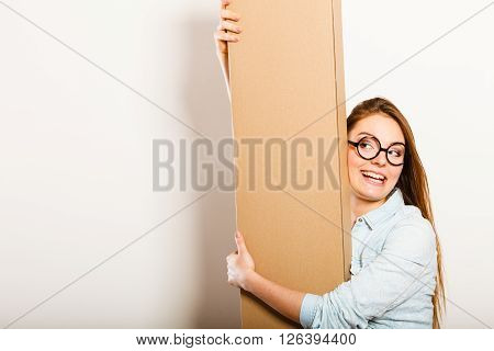 Happy Woman Moving Into Apartment Carrying Box.
