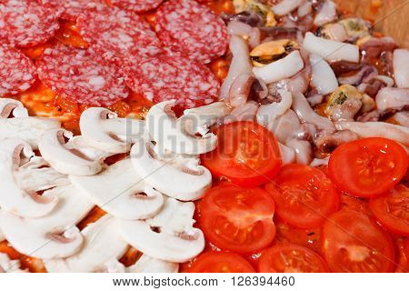 Cooking homemade traditional Italian delicious pizza four seasons with mushrooms seafood and salami.