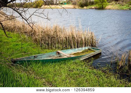 old wooden boat on river shore