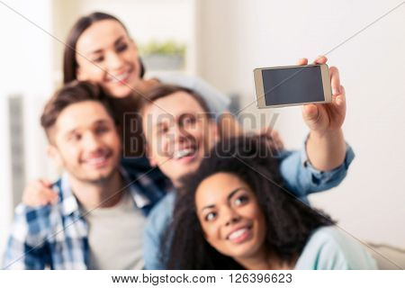 Say cheese.  Selective focus of smart phone in hands of pleasant  handsome guy holding it while making selfies with his friends