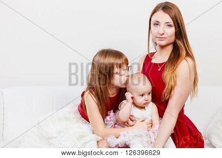 Beauty of motherhood. Happy positive family sitting together. Mommy with two little girls daughters. Three lovely women.