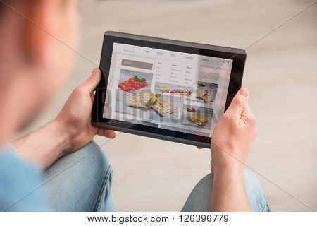 Modern adviser. Close up of tablet in hands of pleasant guy holding it and surfing culinary sites