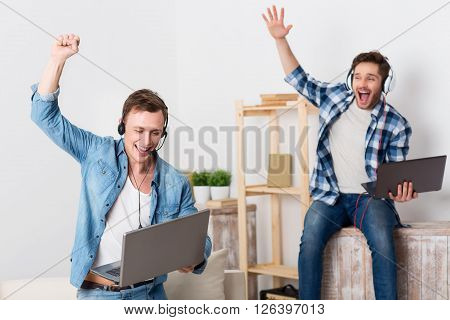 We are the winners.  Cheerful overjoyed handsome  jubilant guys holding laptop and playing games while holding their hands up