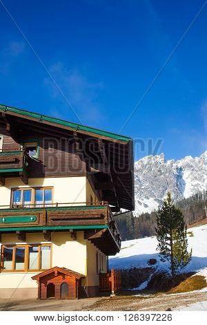Traditional mountain chalets on a cold sunny day with blue sky