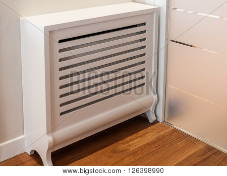 Wooden cover for radiator in home interior