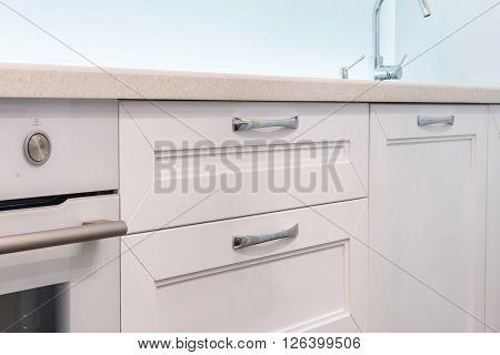 Stainless steel kitchen sink on white granite worktop