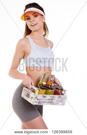 Young happy fit girl with a box of cold pressed vegetable juices