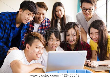 Group of college students watching laptop in classroom