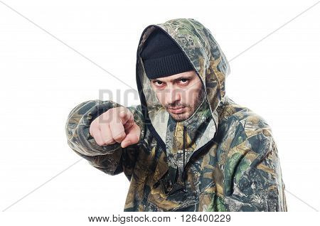 The serious man in a camouflage points a finger forward