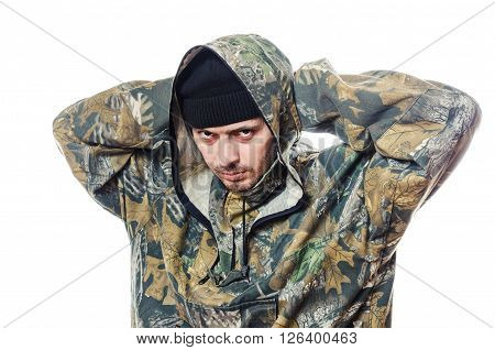 The serious man keeps hands behind the head in a camouflage and looks in a floor